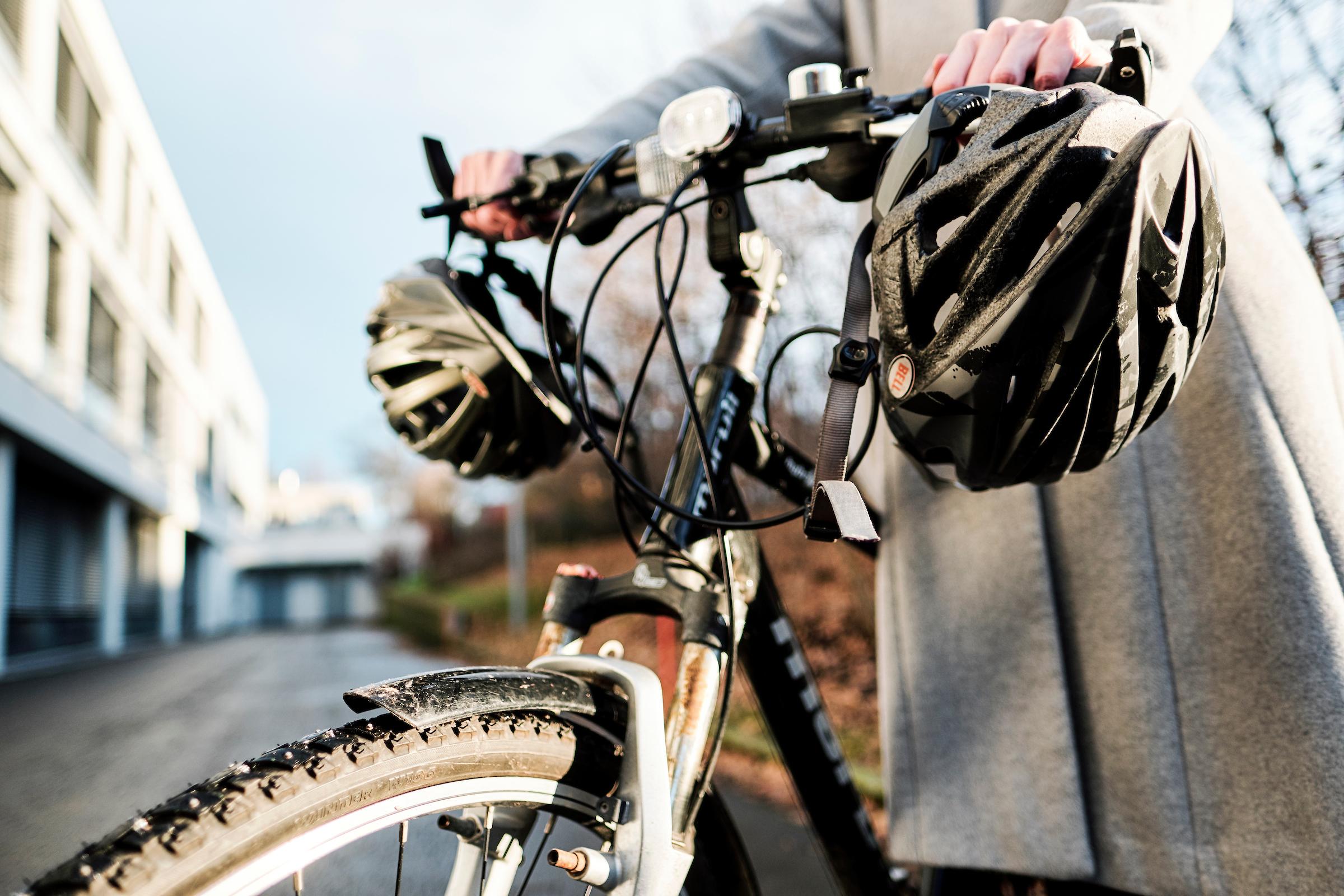 Person med sykkel og to hjelmer