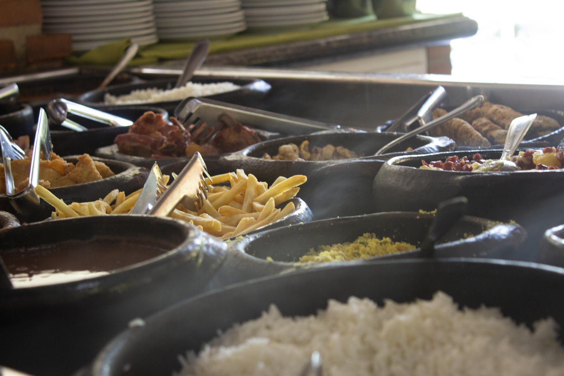 Matbufeet med blant annet ris, pommes frites, kjøtt, i forskjellige beholdere i et varmeskap