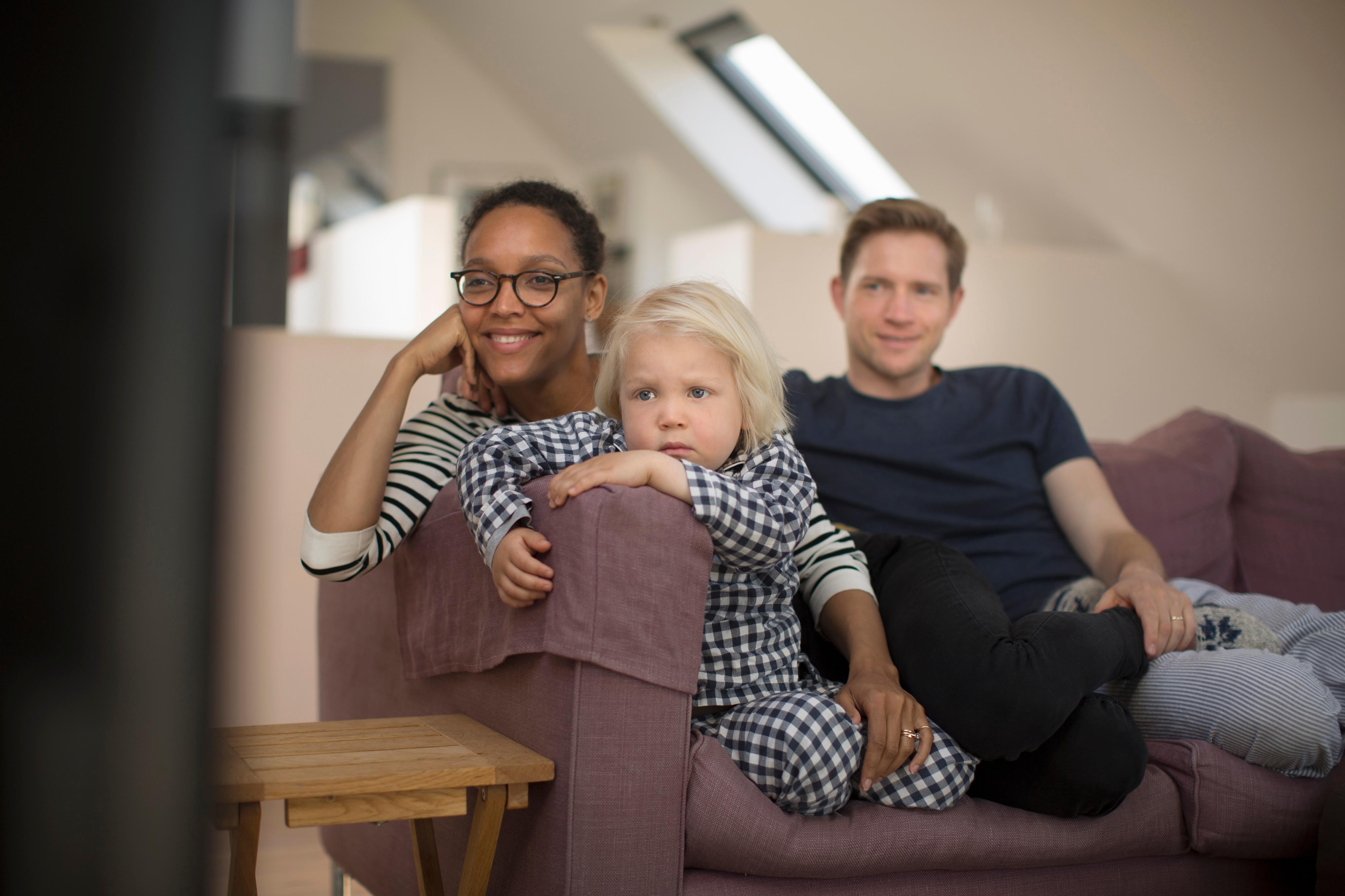 Familie slapper av i sofa