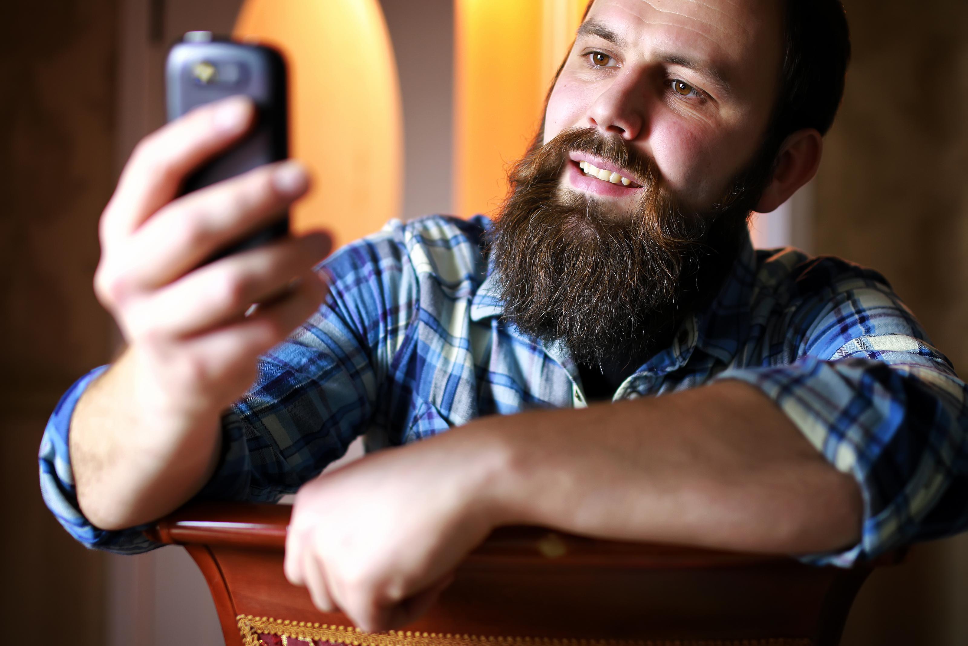 Mann meg skjegg ser på telefon