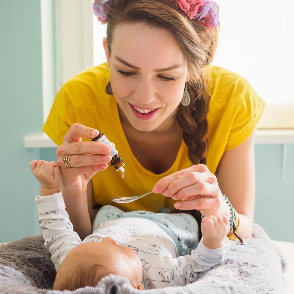 Kvinne som gir vitamintilskudd til et barn