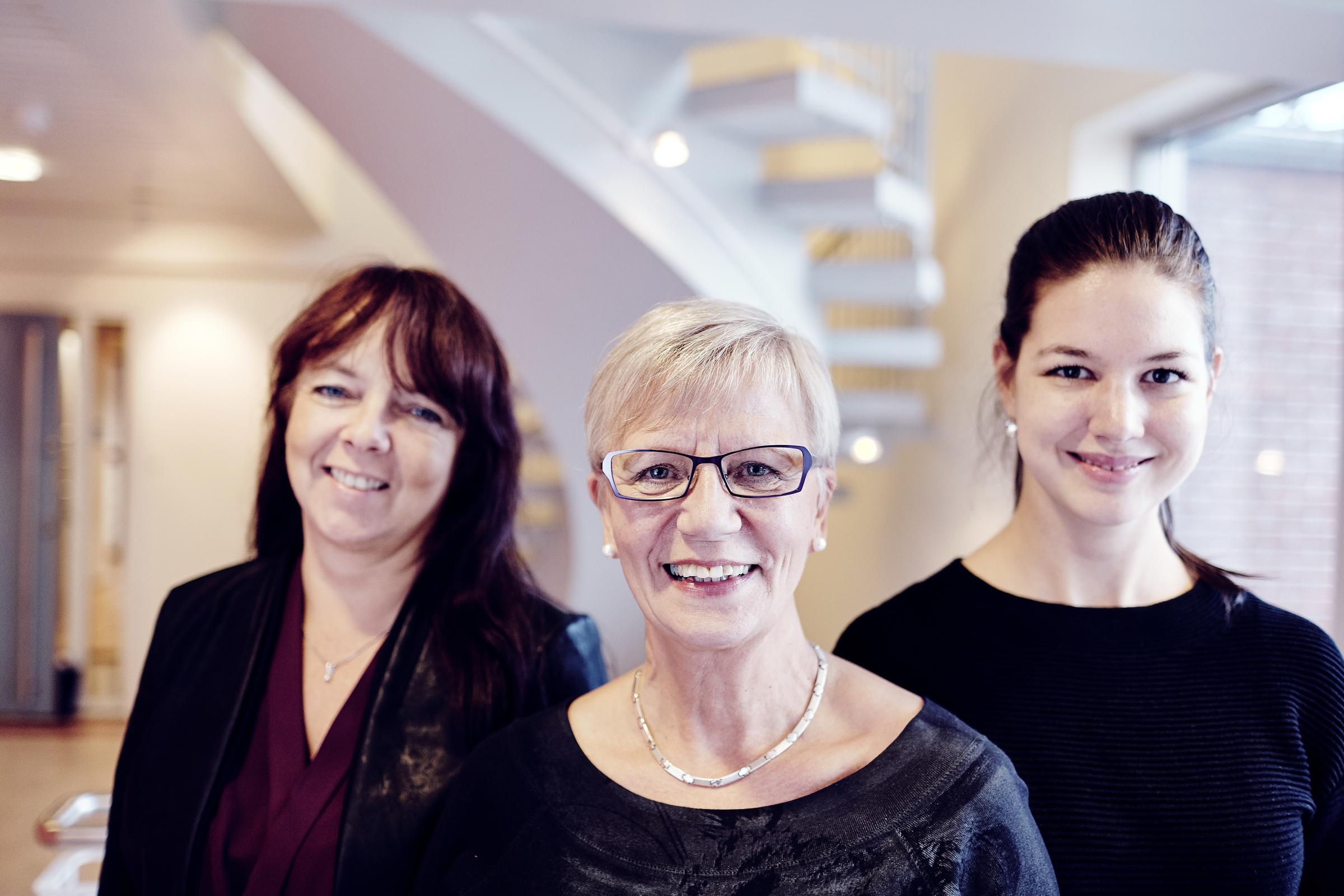 Tre smilende kvinner i ulik alder