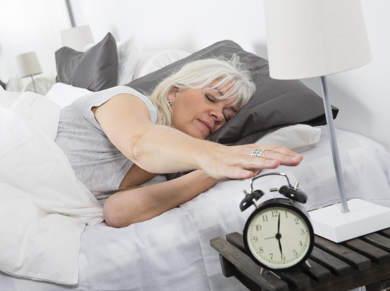 Trøtt kvinne slumrer vekkerklokka