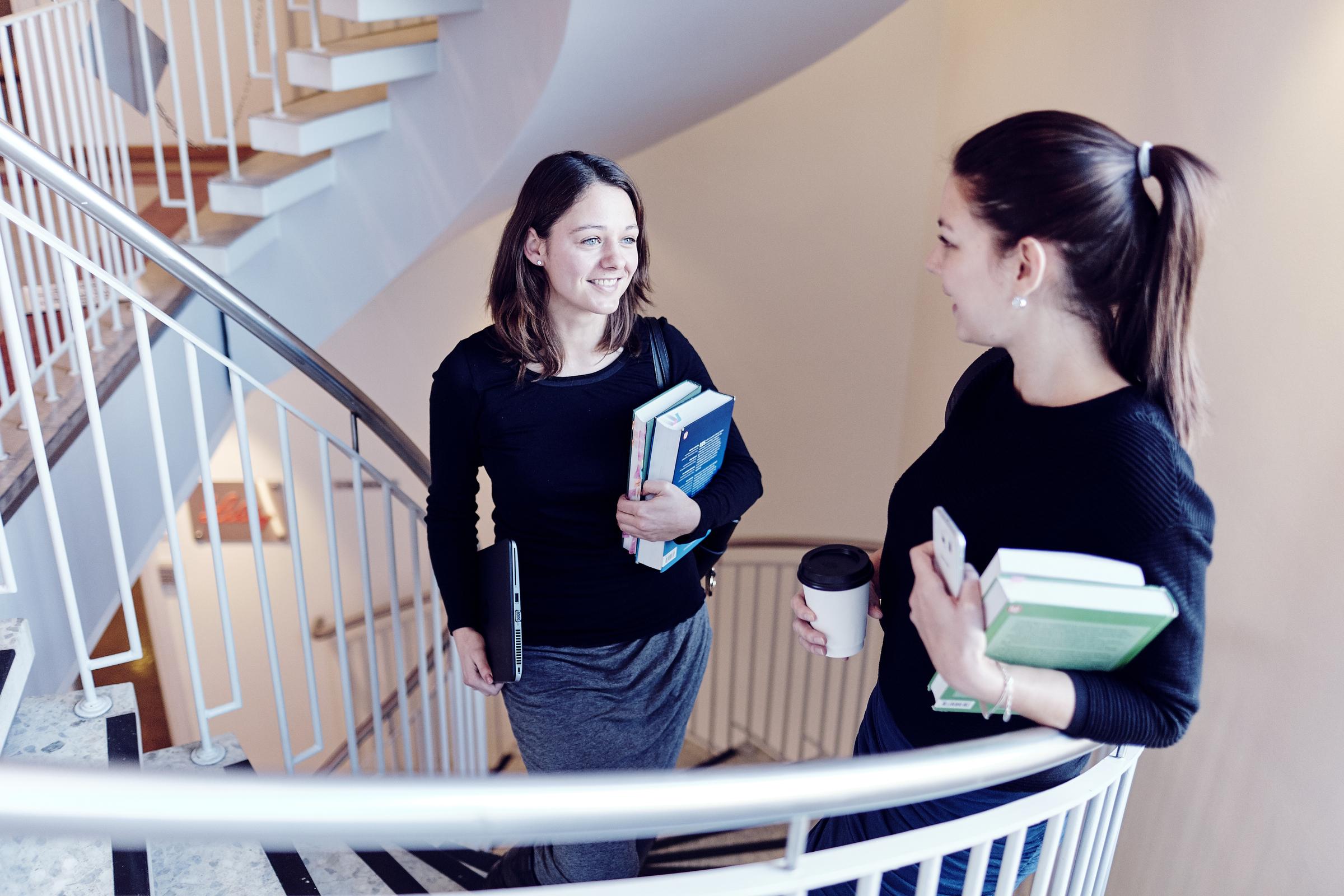 To unge kvinner som holder bøker, i en trapp
