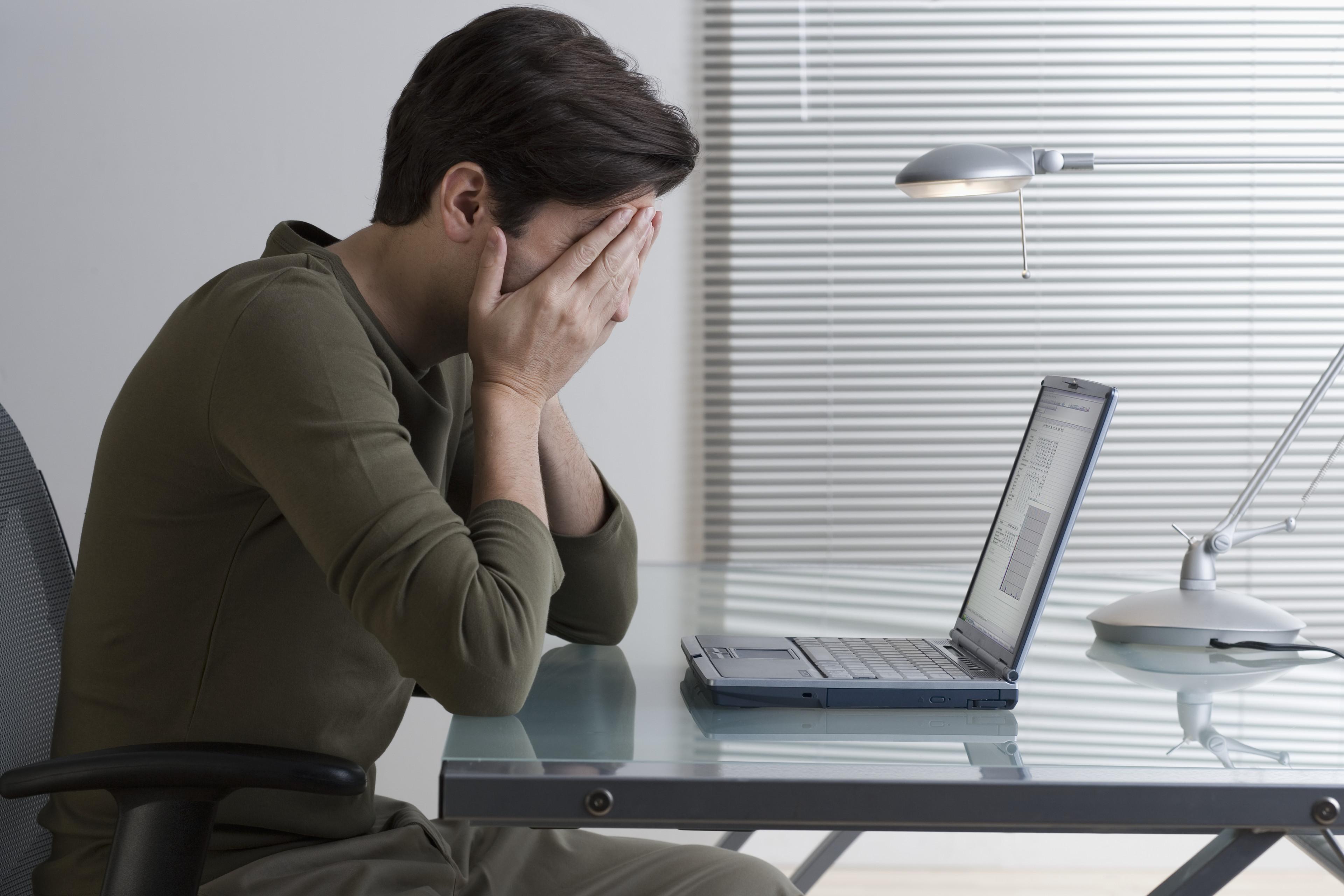 Stresset mann på jobb foran pcen
