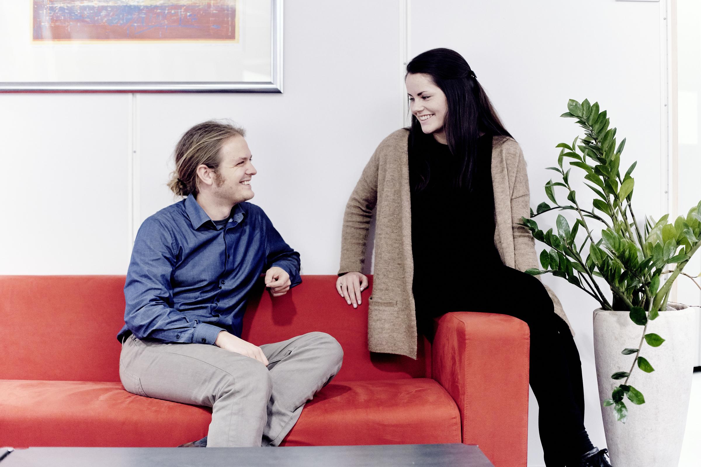 Ungt par i rød sofa