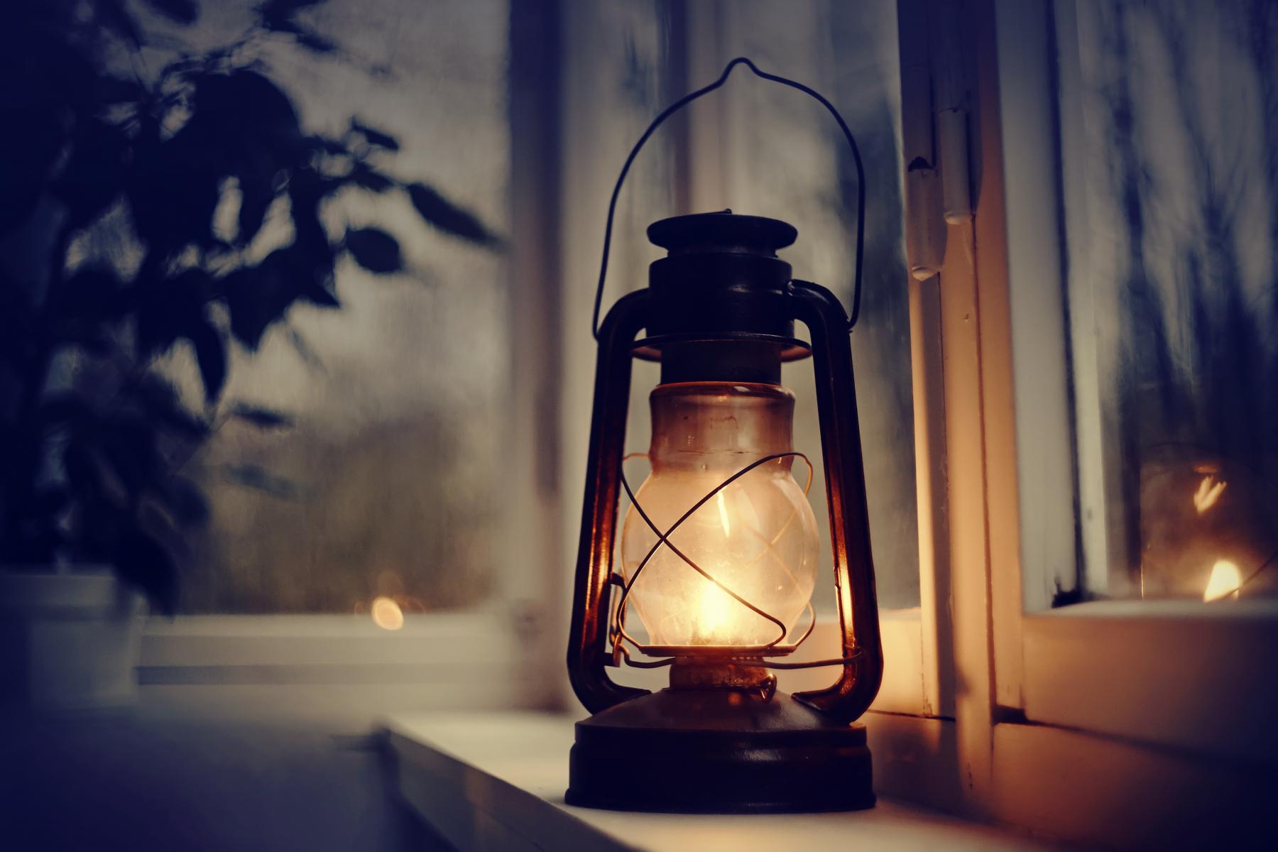 Brennende parafinlampe i vinduspost