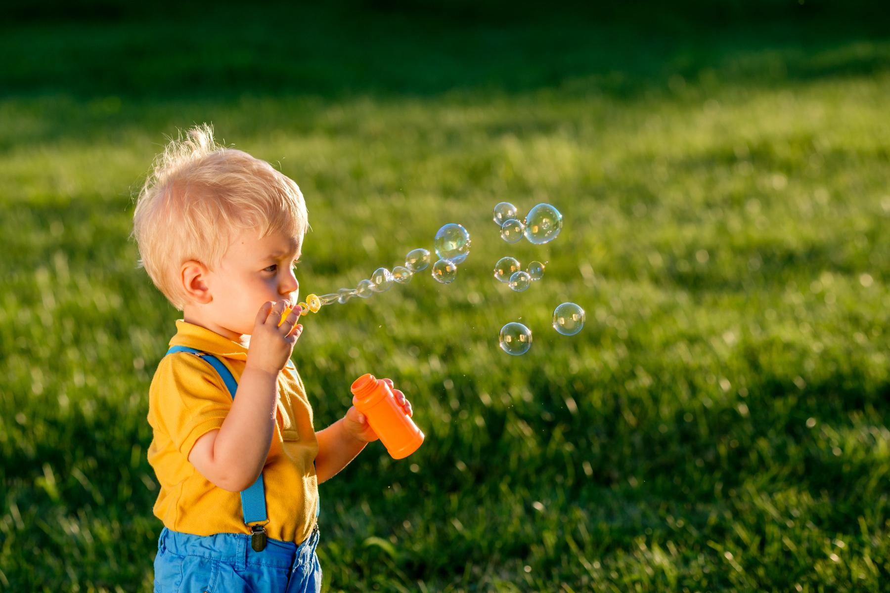 Gutt iført gul t-skjorte og blå bukse, som blåser såpebobler i en grønn eng