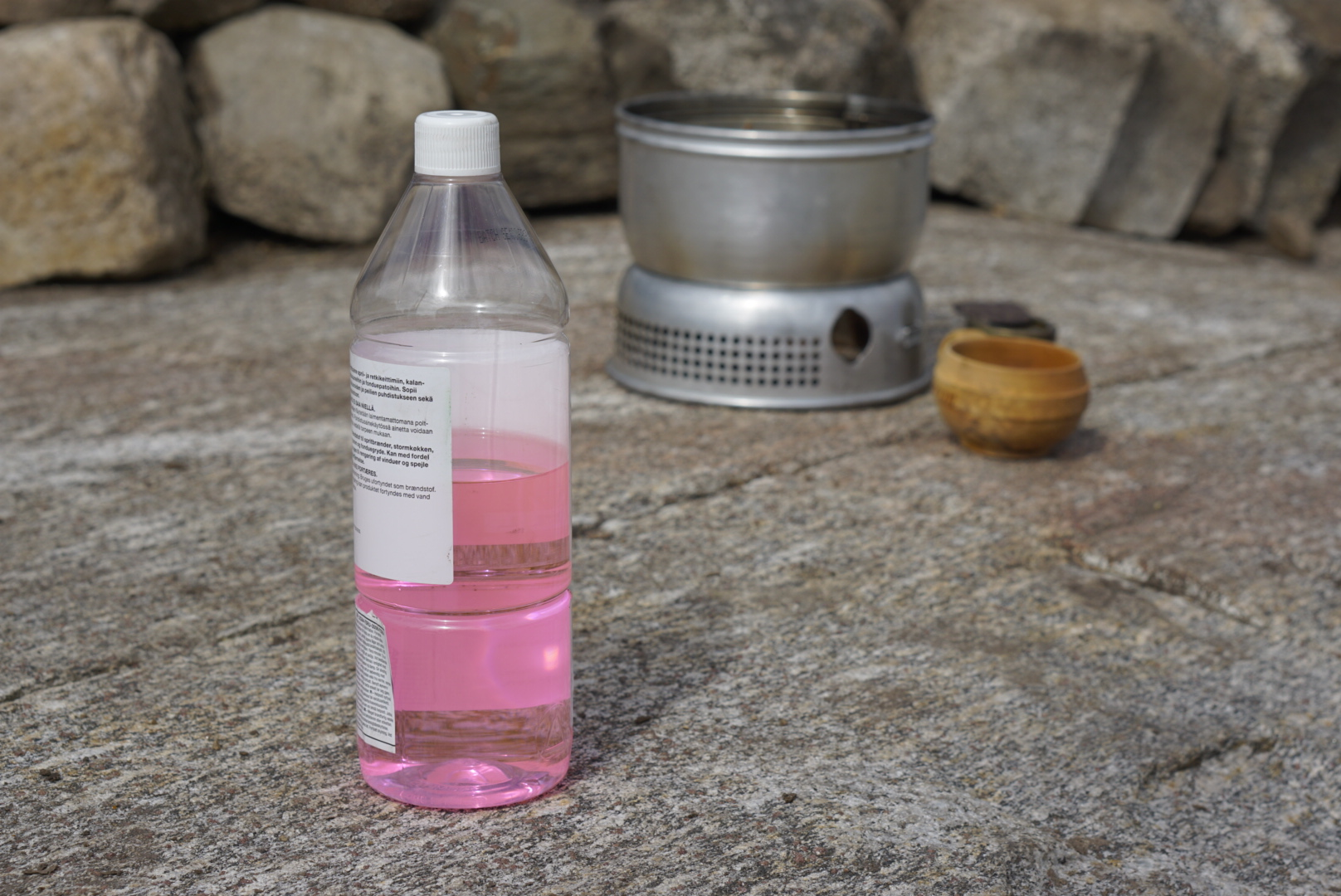 Flaske med rødsprit stående ved siden av stormkjøkken