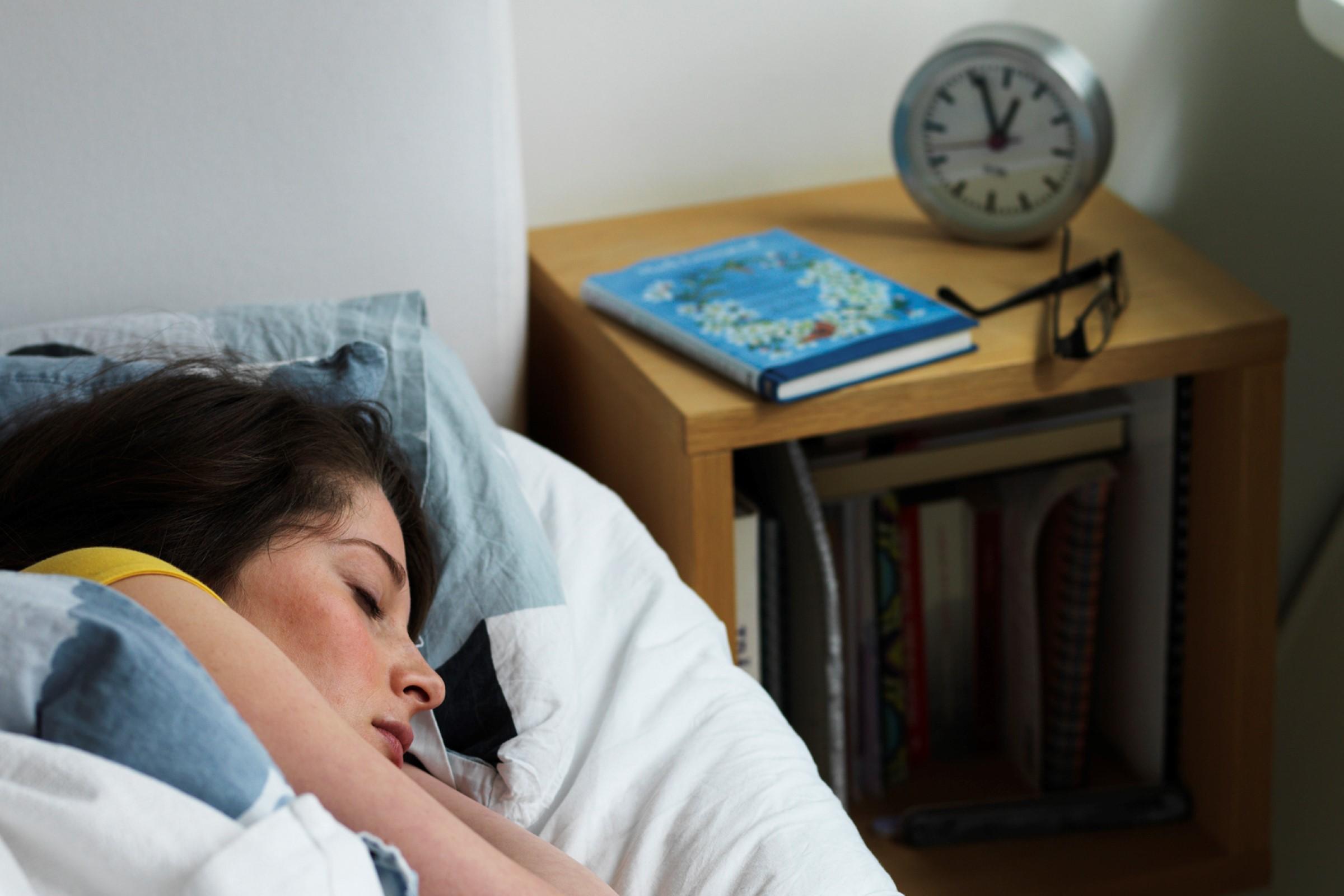 Sovende dame ligger i sengen