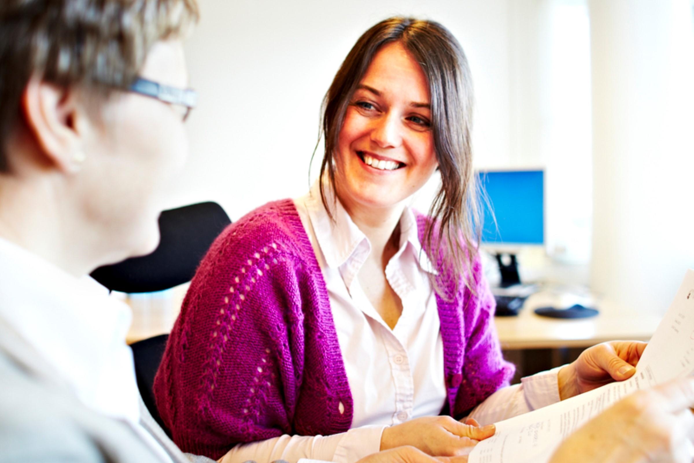 To kvinner smiler og snakker sammen
