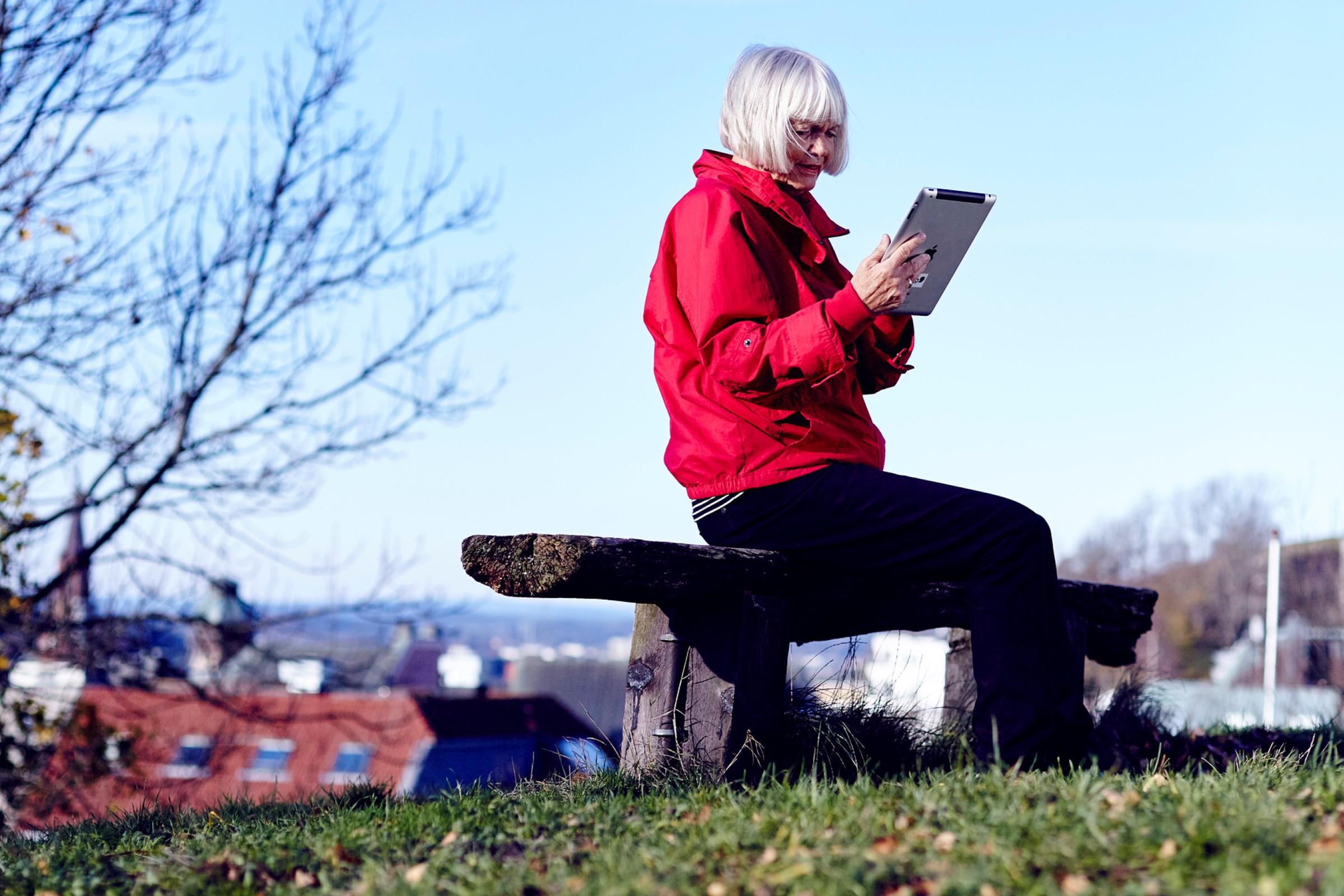 Eldre kvinne på benk med nettbrett
