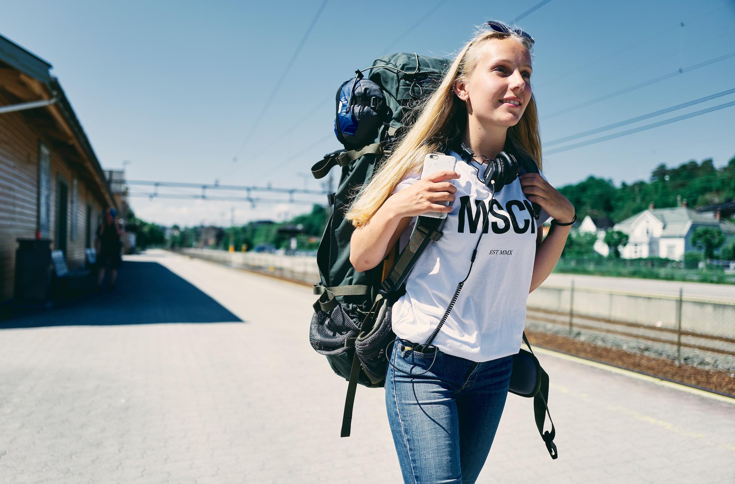Ung kvinne med ryggsekk på jernbaneplattform