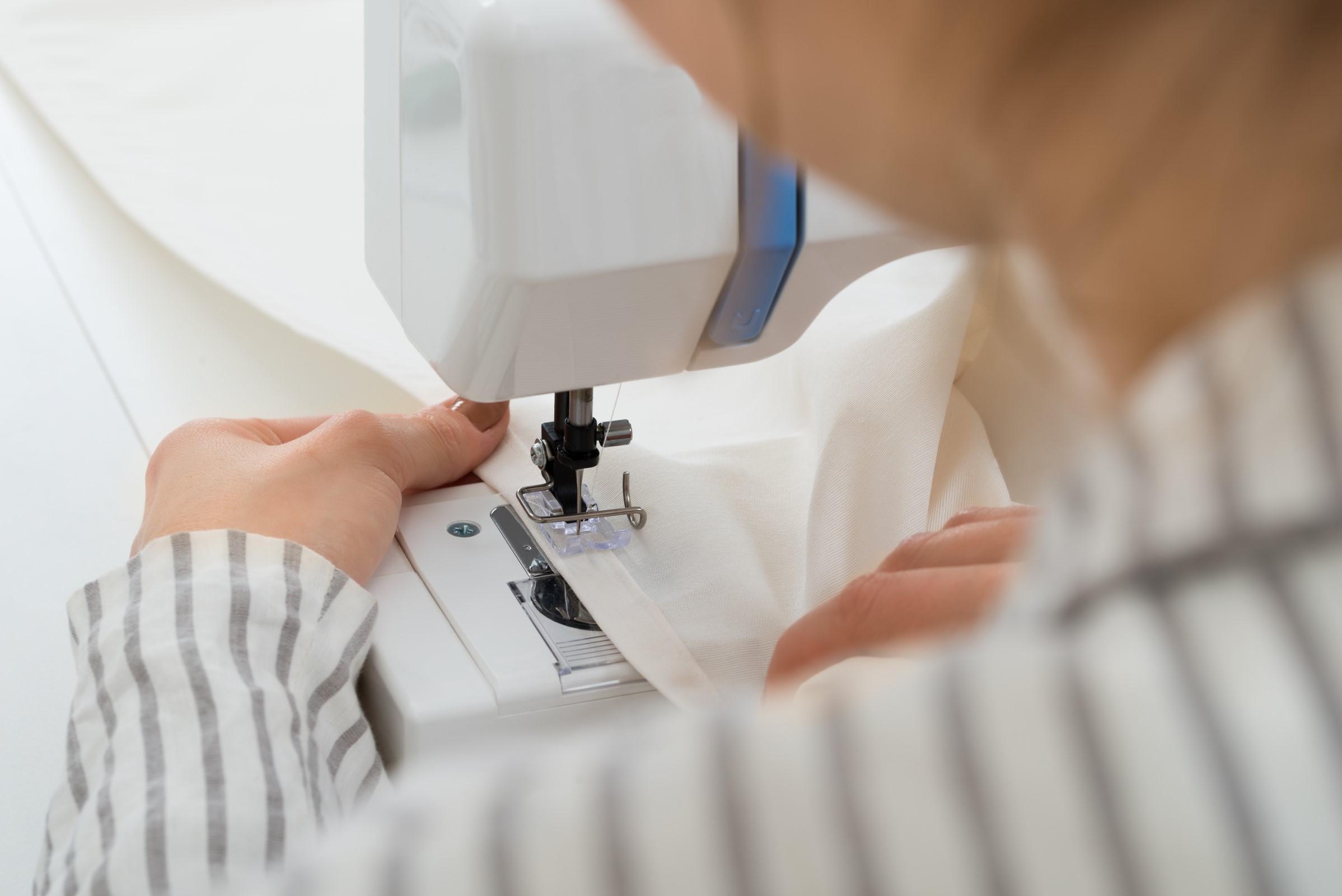 Dame som syr på symaskinen sin