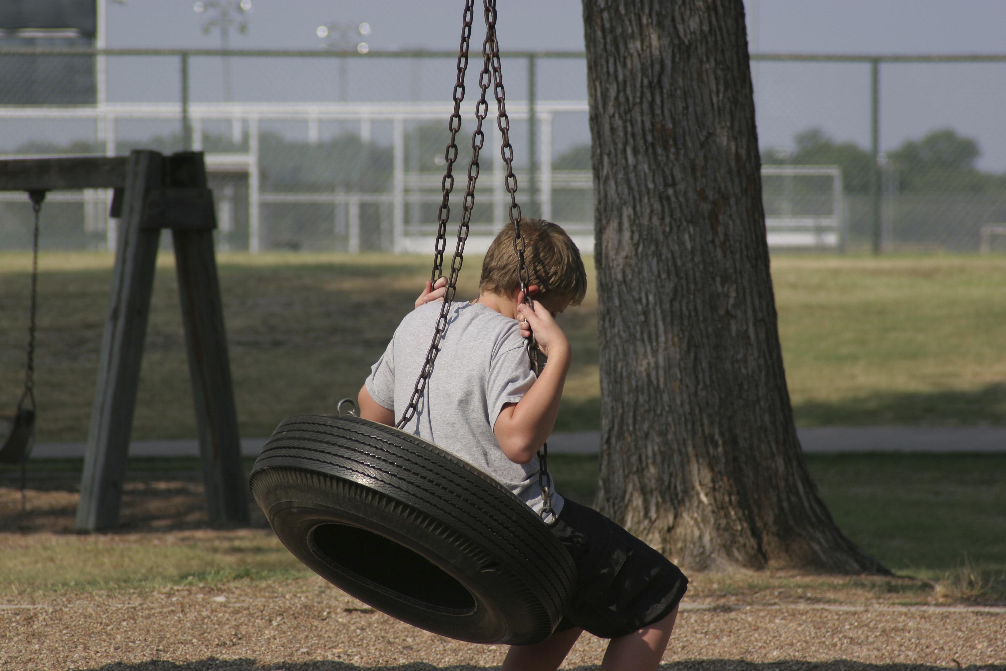 En gutt sitter på en huske og virker trist.