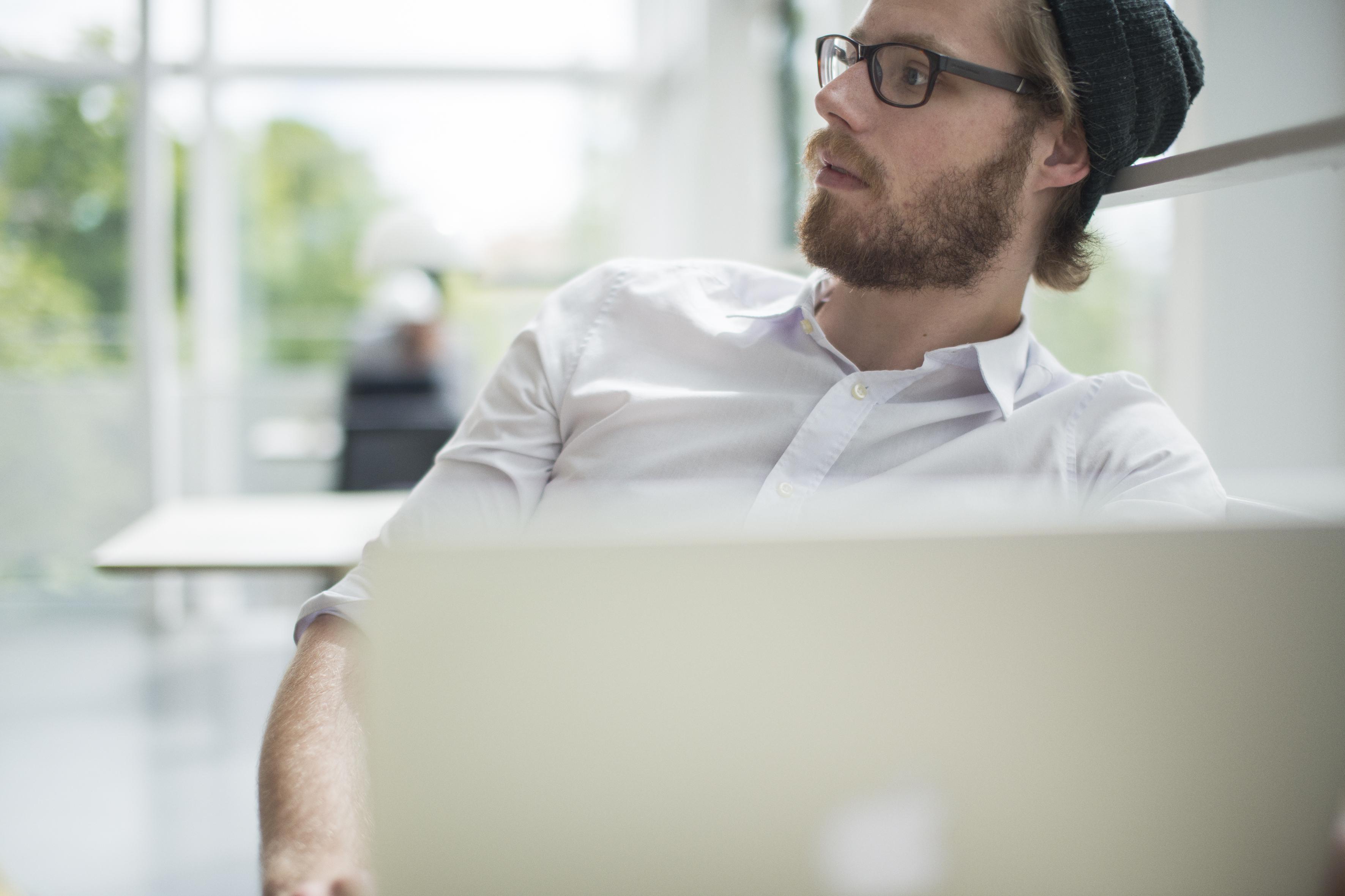 Mann sitter bak PC skjerm