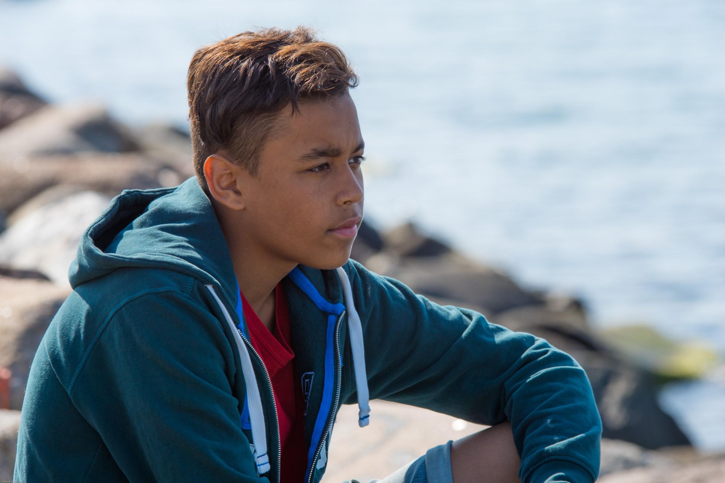 Bilde av en tankefull ung gutt som sitter ved vannet