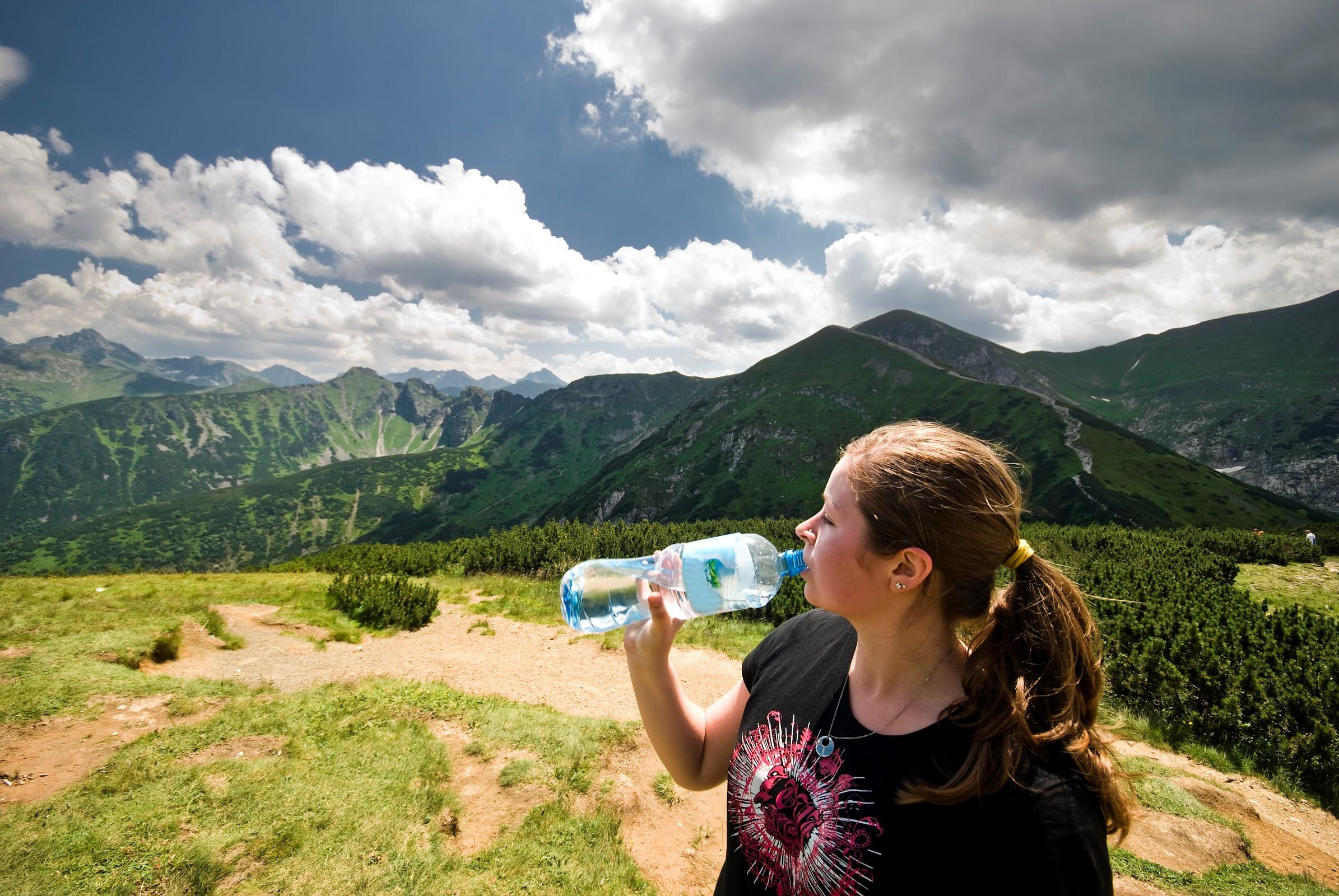 kvinne drikker fra flaske