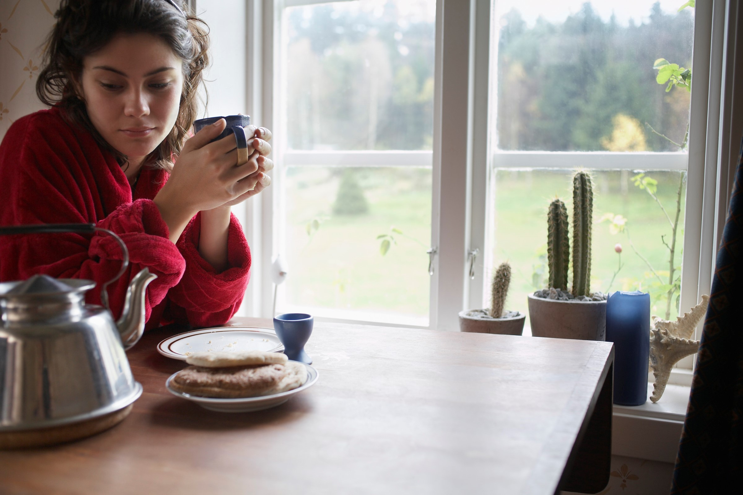 Kvinne sitter ved vinduet og drikker te