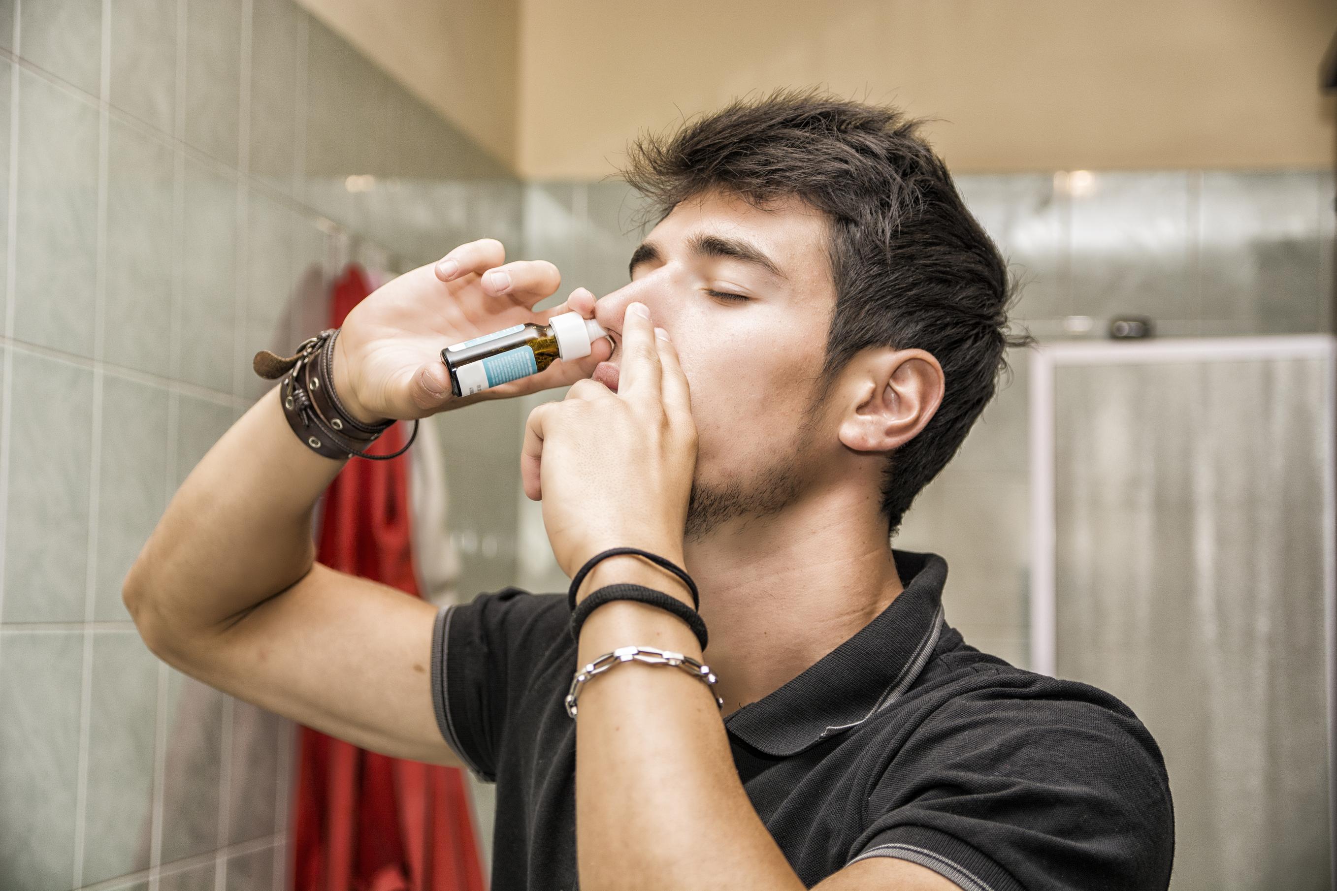Mann holder nesespray inn i nesen