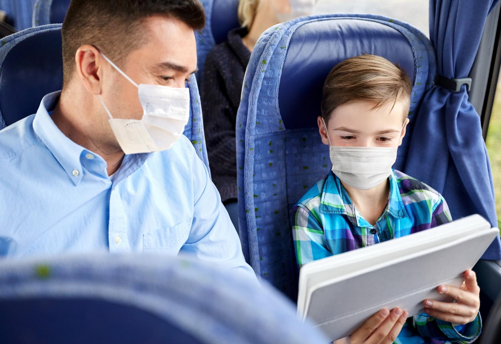 Mann og gutt iført munnbind, som ser på nettbrett under en busstur.