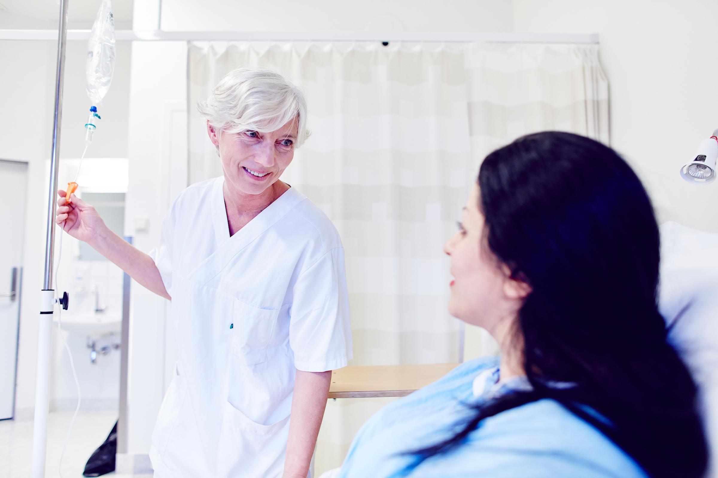Smilende lege og pasient snakker sammen