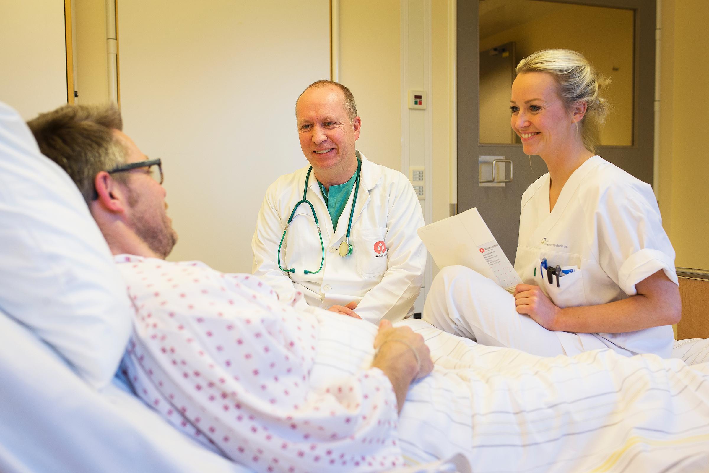 Mannlig pasient snakker med to leger