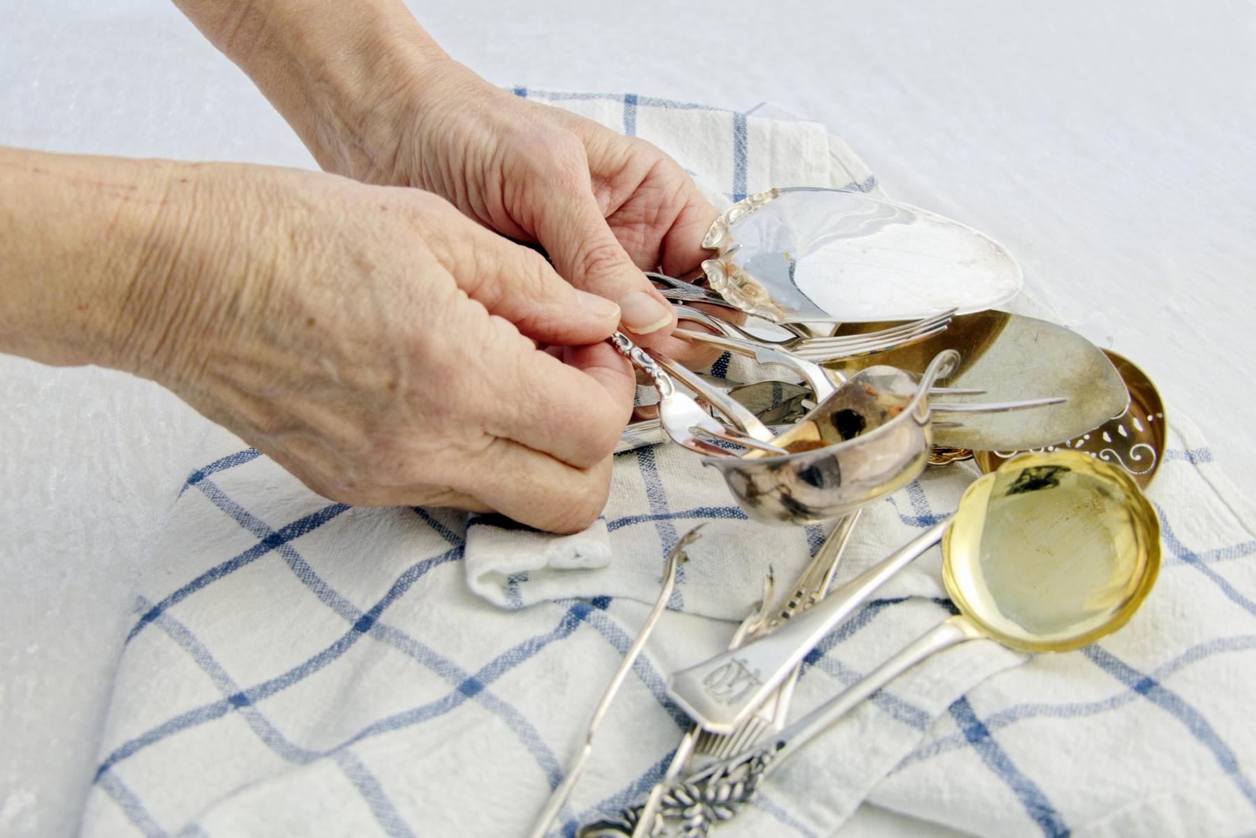 Forskjellig bestikk som pusses med sølvpuss og tørkes på håndkle