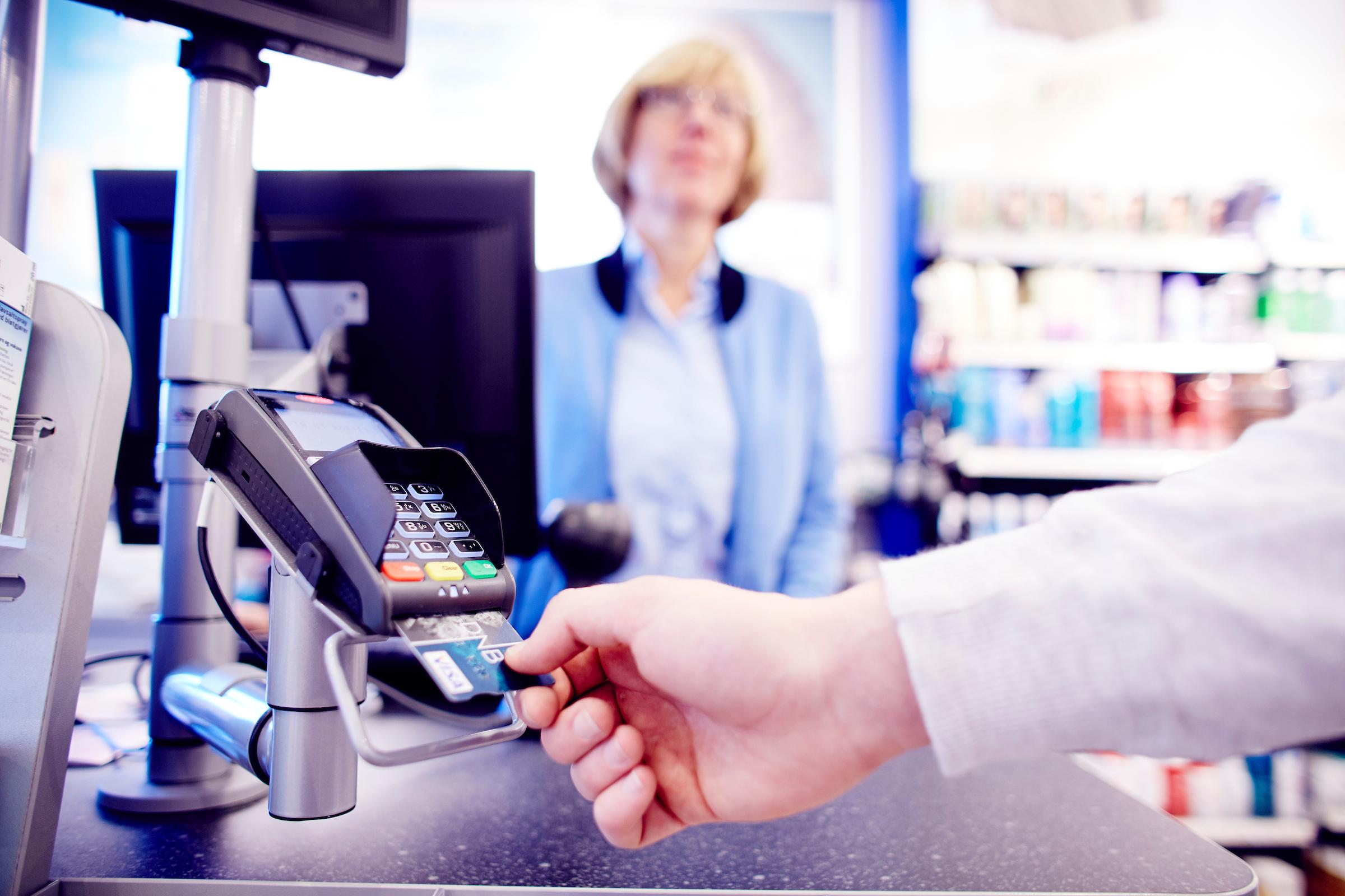 Apotekkunde bruker betalingsterminal på apotek