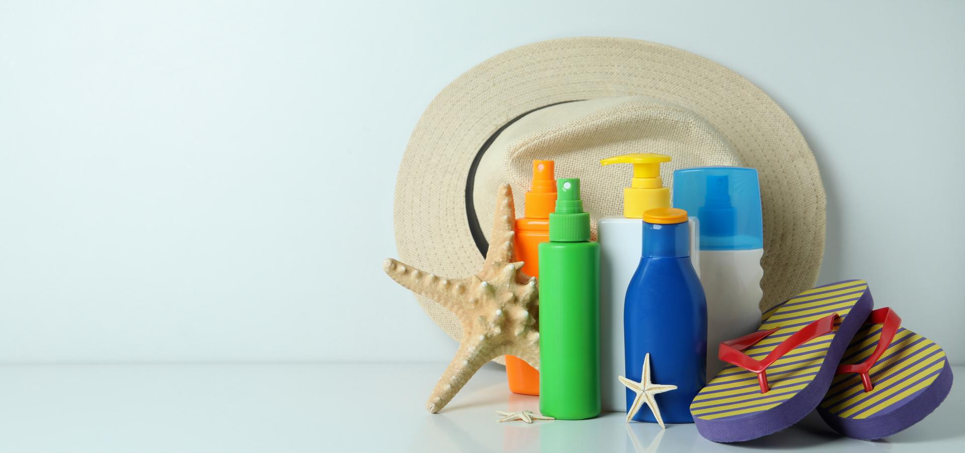 Forskjellige solkremprodukter med badesandaler og hatt.