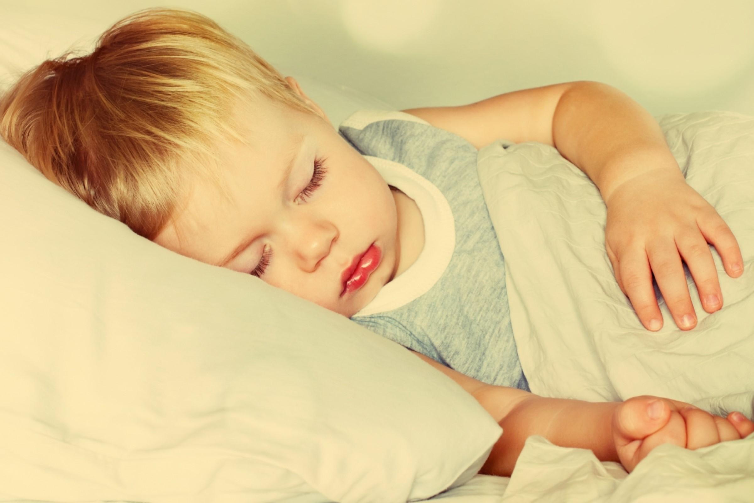 Barn som ligger i sengen