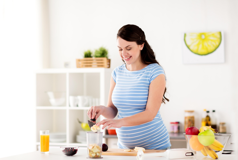 Gravid kvinne lager smoothie