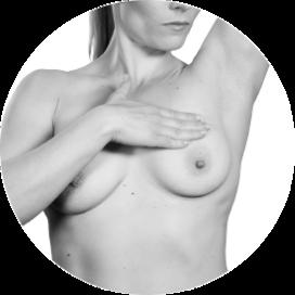 Kvinne som løfter en arm og undersøker brystet med den andre