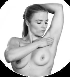 Kvinne undersøker brystene og leter etter kuler i armhulen