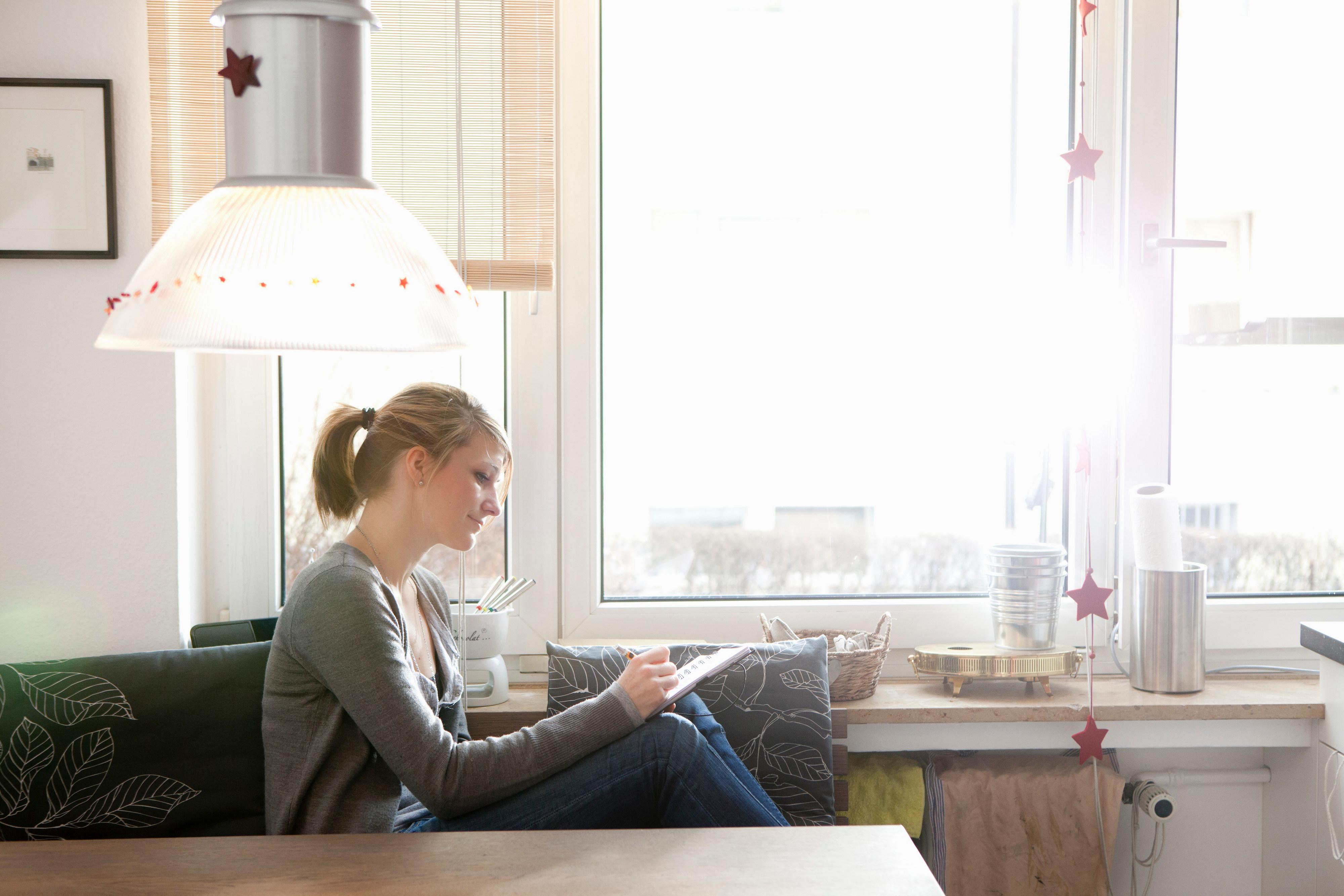 Kvinne skriver i sofaen