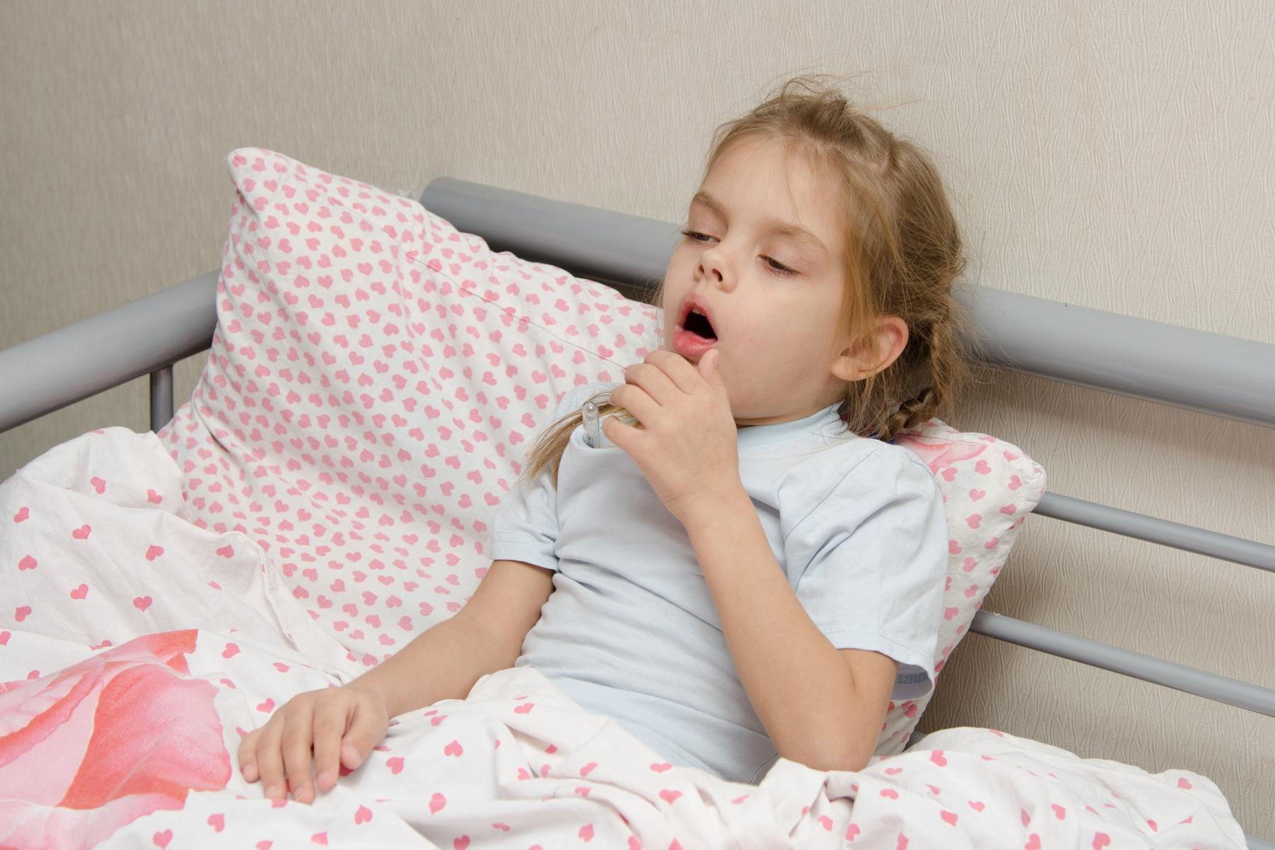 Barn som ligger i sengen og hoster.
