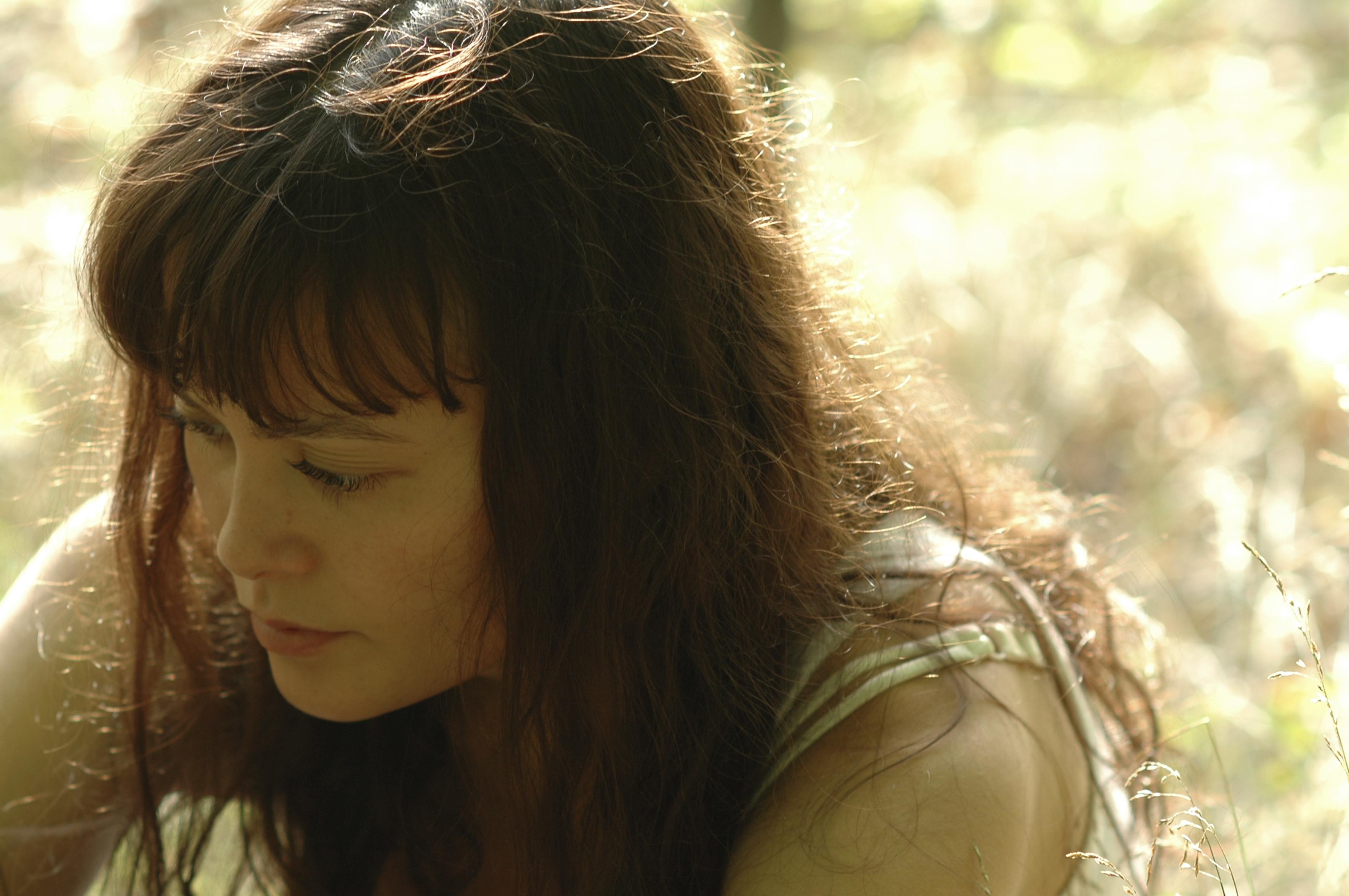 Kvinne som ligger i gresset og ser nedover
