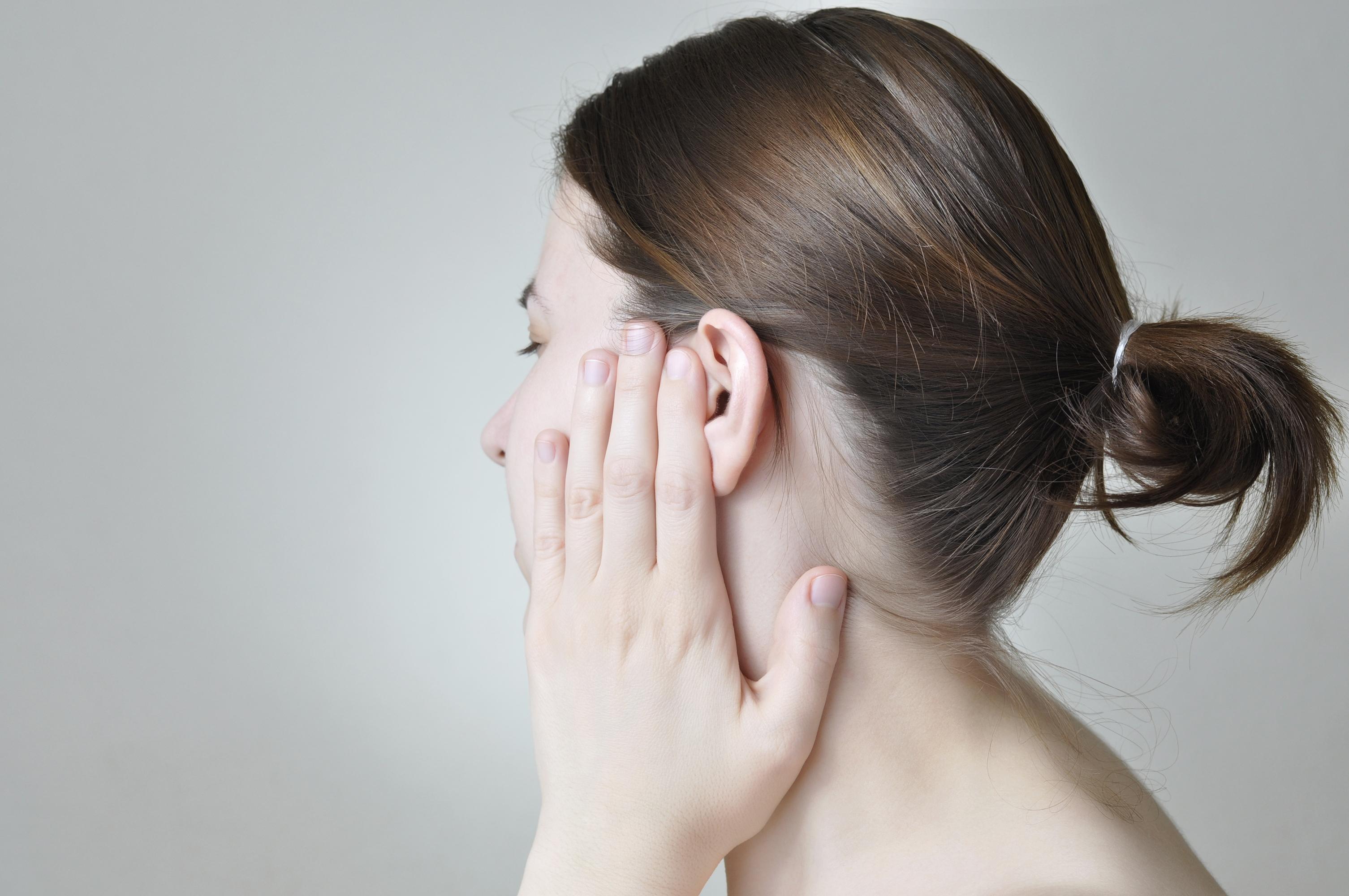 Bilde av kvinne som tar på øret sitt