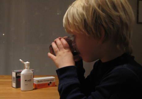 Lite barn med lys lugg som drikker medisinsk kull etter forgiftningsuhell