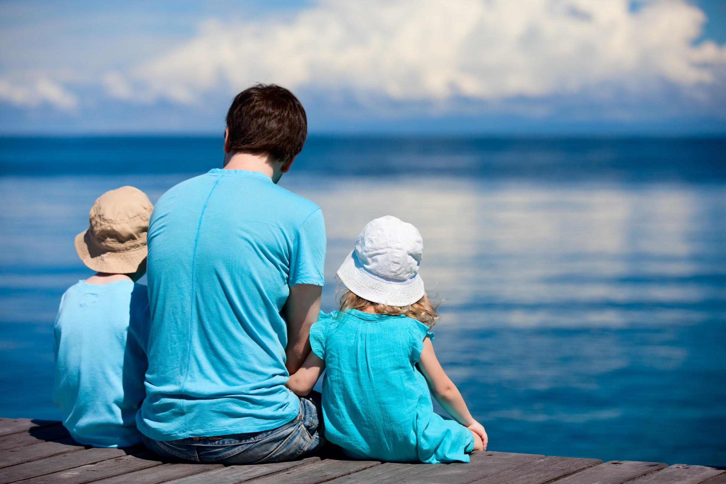 En familie sitter ved vannkanten