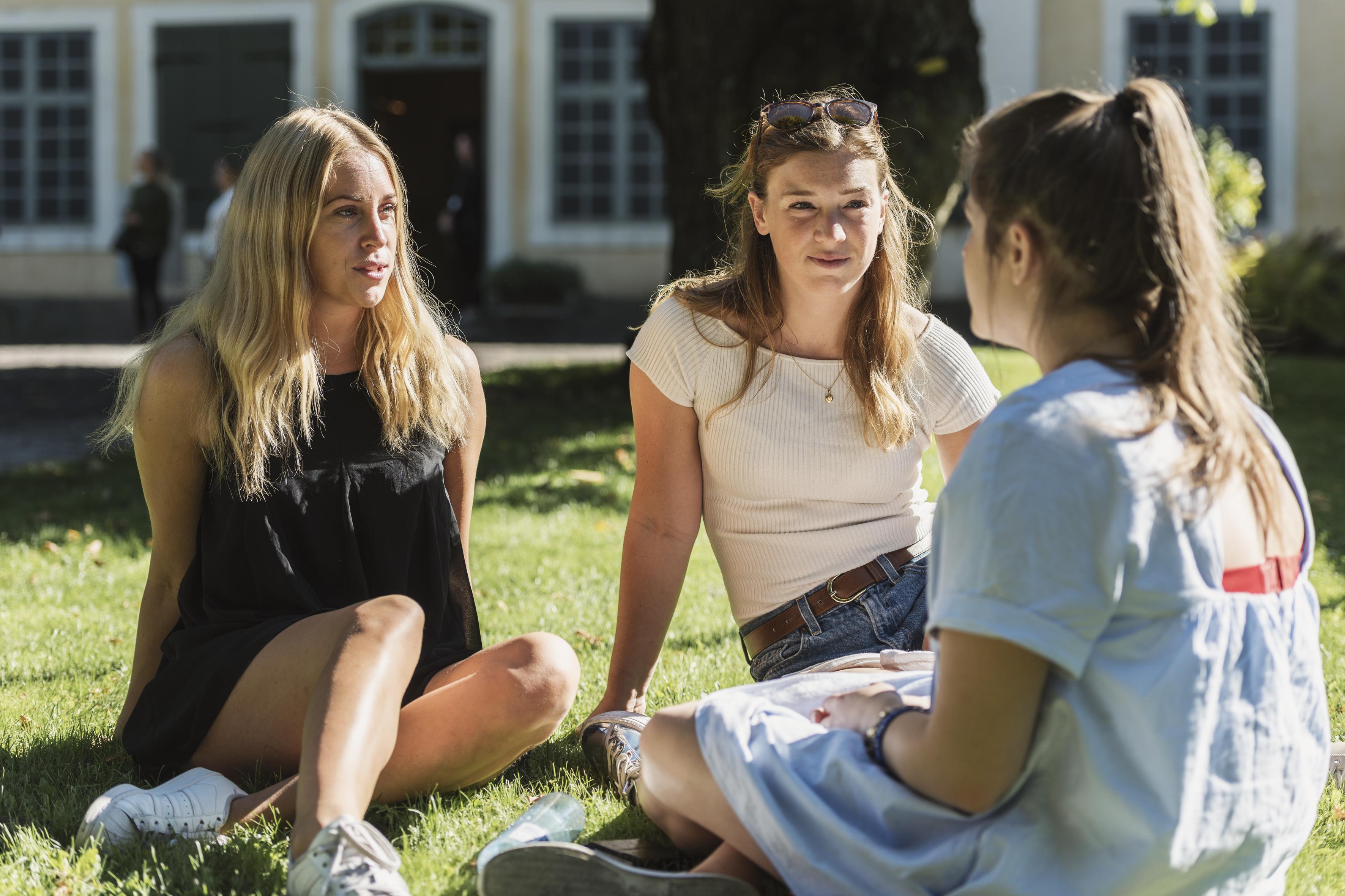 Tre unge kvinner sitter i gresset og prater