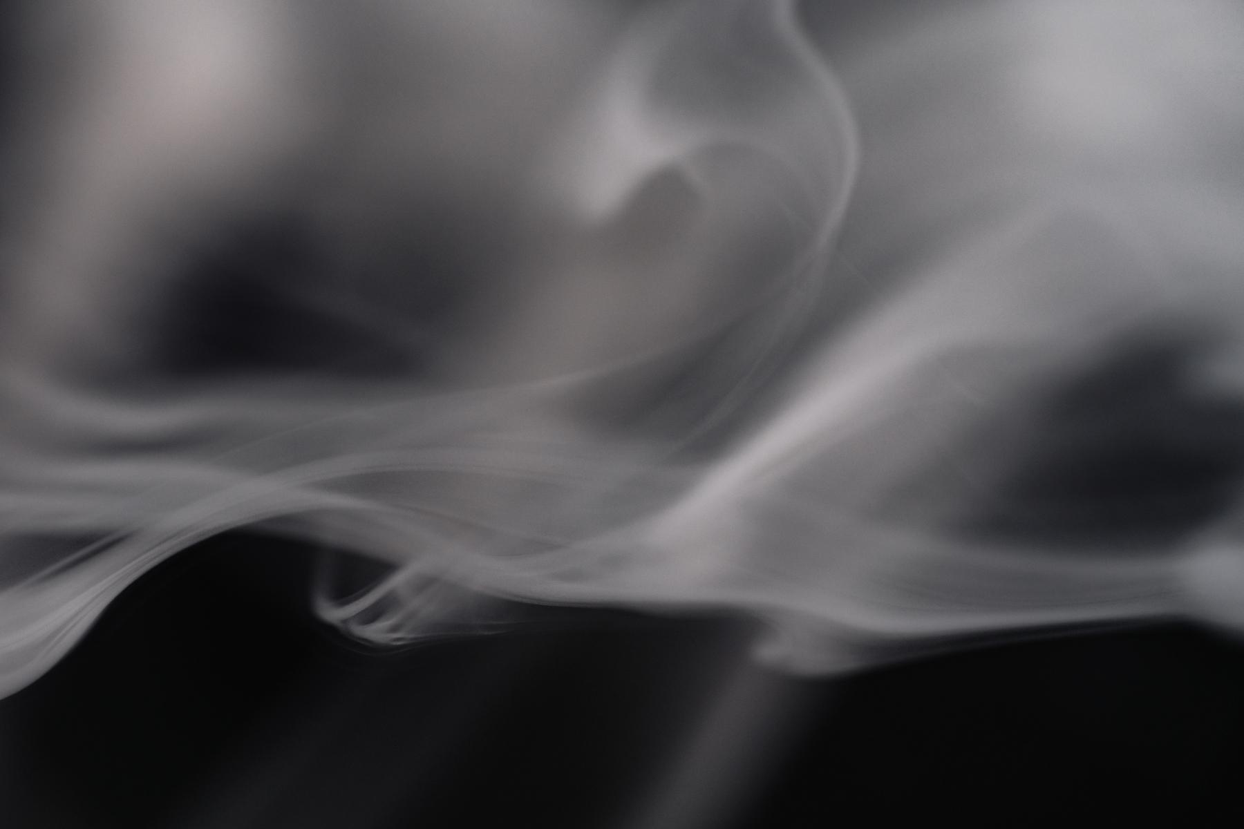 Illustrasjon av grå røyk mot svart bakgrunn