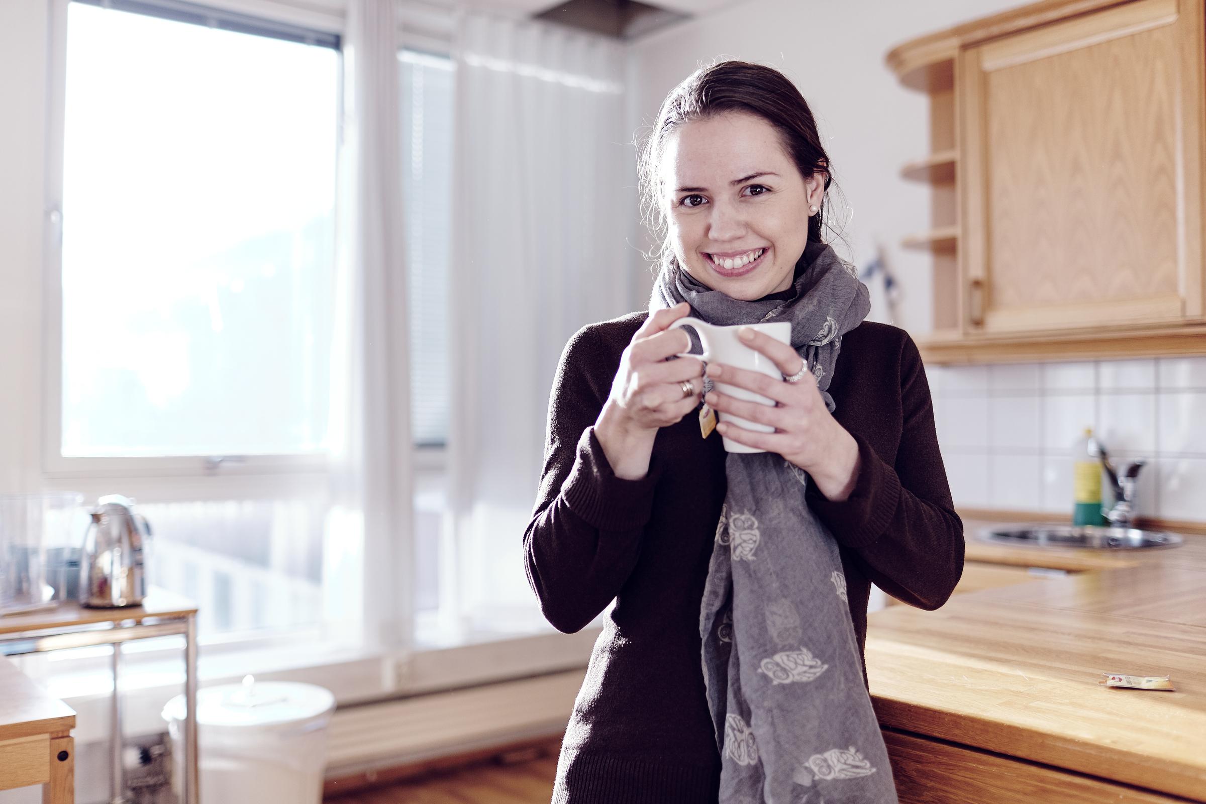 Ung kvinne holder kopp på kjøkken