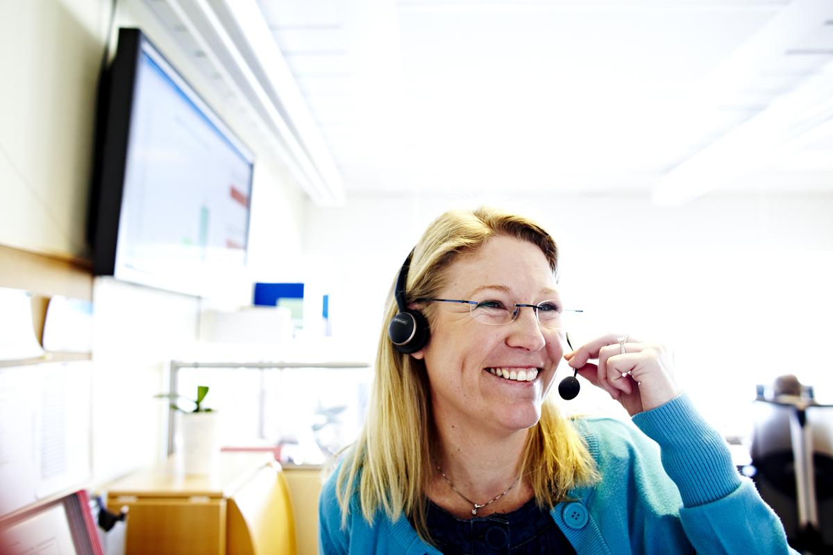 Smilende kvinne som har telefonvakt