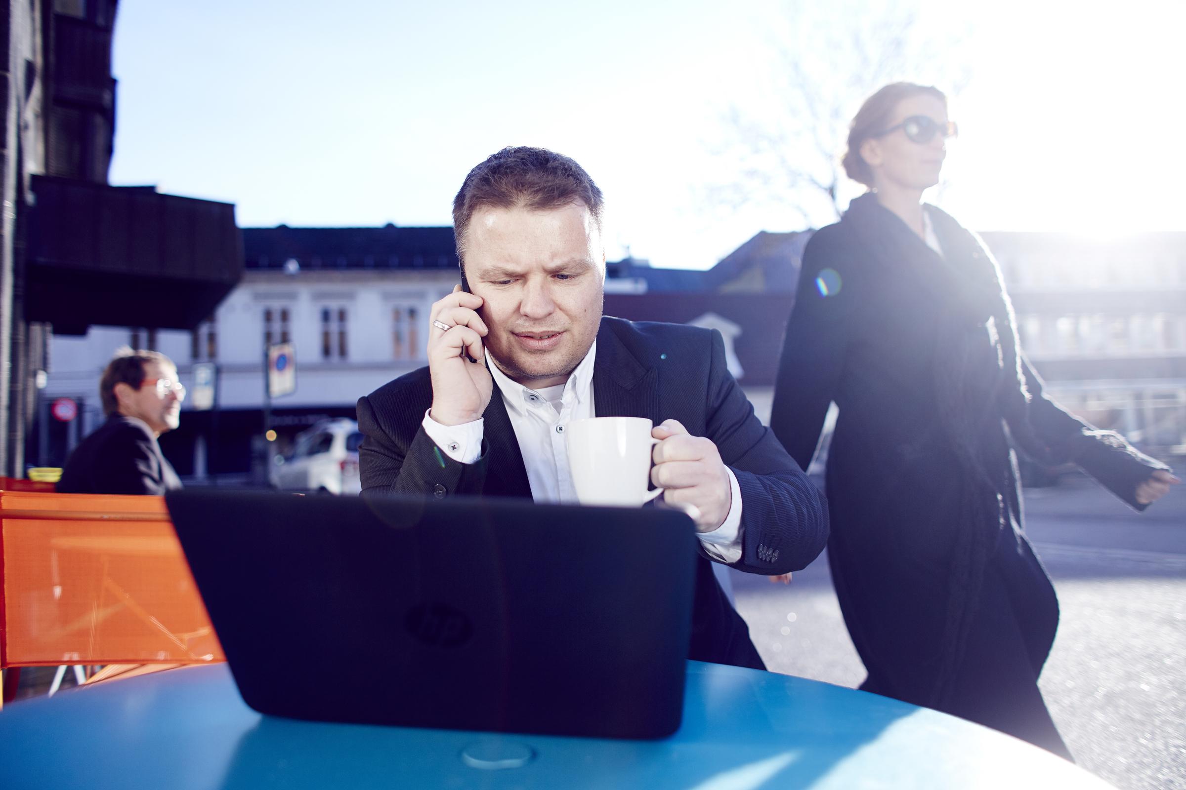 Forretningsmann jobber på data og snakker i mobil.