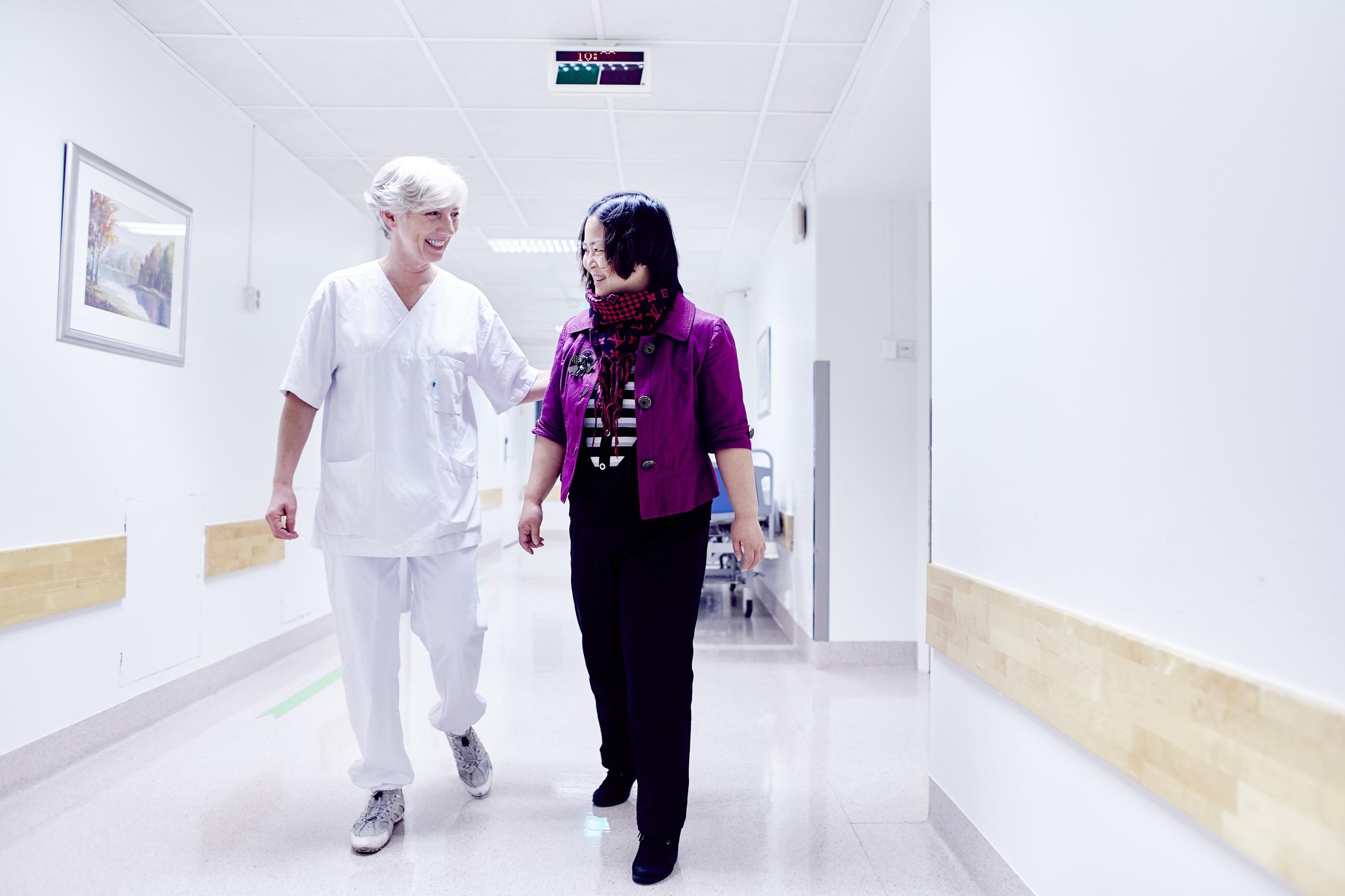 Smilende sykepleier følger pasient nedover sykehuskorridor.
